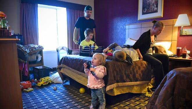 LillyAnn Hadammek watches television as her mother Kristy and father Andrew get ready to go to work Friday in their room in a St. Cloud hotel. The family of five shares the room with Kristy's mother Deb Cedergren.