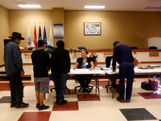 At center, polling official Ronda Johnson helps voters