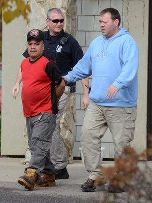 Elias Lopez, 43, is escorted Oct. 21 from MiZarape Restaurant in Milford by Milford Police Lt. Matt Brumm, right, and a member of the U.S. Immigration and Customs Enforcement Task Force. Lopez' illegal alien status was discovered the previous Sunday after he reportedly harassed a 13-year-old girl in downtown Milford.