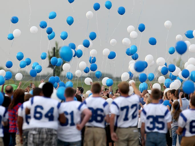 Mourners release balloons on the football field during a memorial service for Jason Moran, Wednesday, June 11, 2014, at Franklin Community High School. Moran and Michael Chadbourne died after coming to the aid of Sarah McLevish who was swept below part of the dam on the Big Blue River while swimming in southern Johnson County.