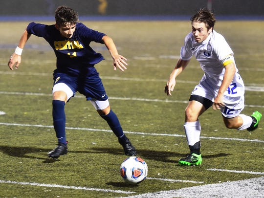 Lakeland's David Wojciechowski (right) races down the sideline against a Walled Lake Central player.