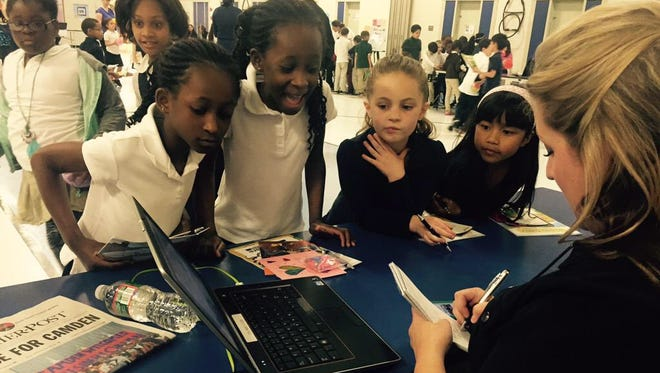 Courier-Post staff writer Carly Q. Romalino works with Winslow School 4 second graders to write a story about its career fair in 2015.