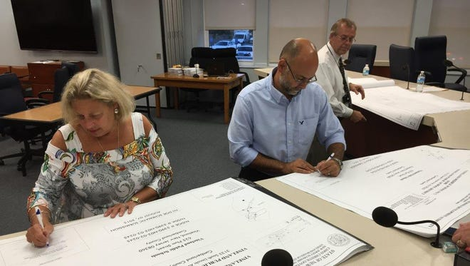 Superintendent Mary Gruccio and School Board President Scott English sign the schematic plans for Middle School No. 2 back in August, presented to them by Wayne Weaver, (right) the district's director of facilities.