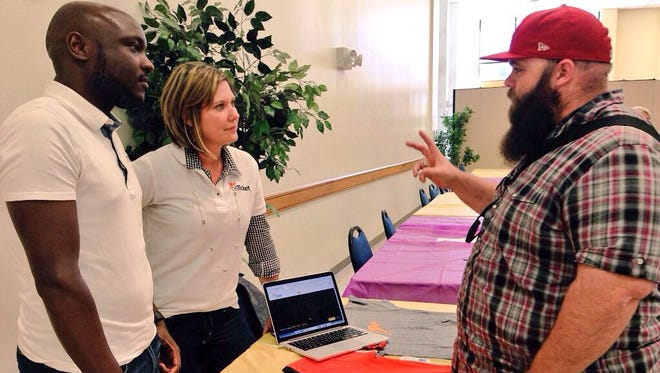 Louisiana State University of Alexandria senior Brandon Creighton (right) talks with Peter Rotich and Karen Vincent with Enhancesoft at a job fair Tuesday.