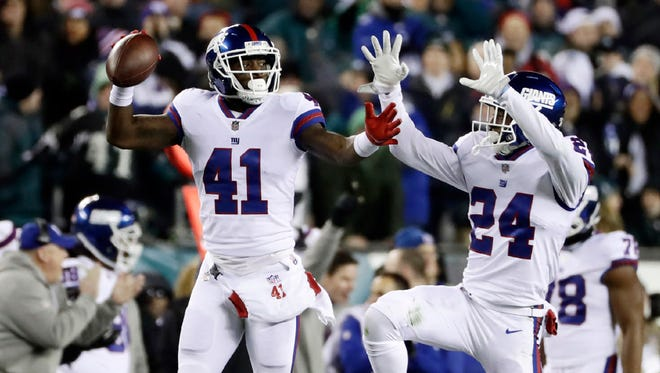 Giants' Dominique Rodgers-Cromartie (41) and Eli Apple celebrate after Rodgers-Cromartie's interception during the first half of Thursday's game against the Eagles.
