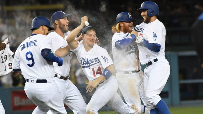 Los Angeles Dodgers left fielder Chris Taylor (3) celebrates with catcher Yasmani Grandal (9) center fielder Enrique Hernandez (14) starting pitcher Clayton Kershaw (22) and third baseman Justin Turner (10) after he hits a walk off RBI hit in the ninth inning against the Arizona Diamondbacks at Dodger Stadium.