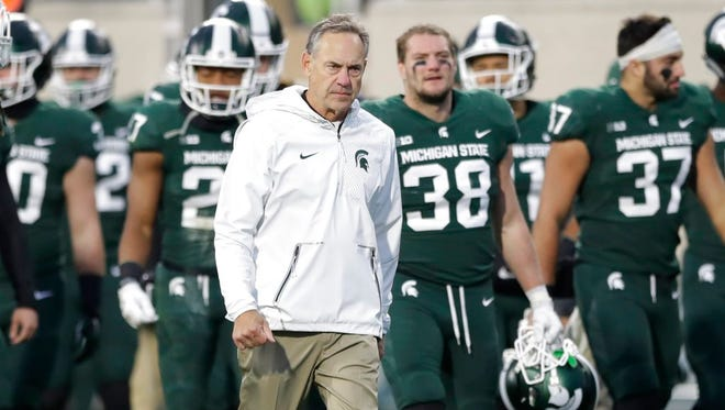 Michigan State head coach Mark Dantonio and team walk off the field after a storm warning during the first half against Penn State on Saturday.