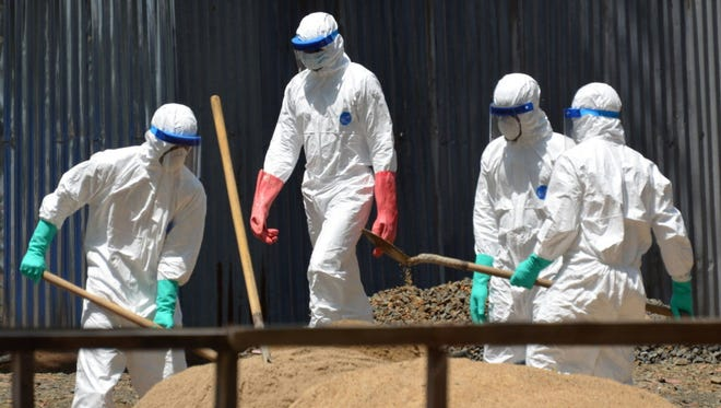Health workers from the Liberian Red Cross shovel sand which will be used to absorb fluids emitted from the bodies of Ebola victims.