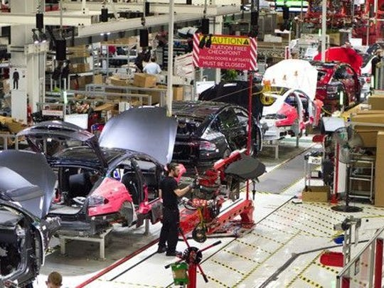 Partially-assembled Model X SUVs move down an assembly line at Tesla's Fremont, California factory.