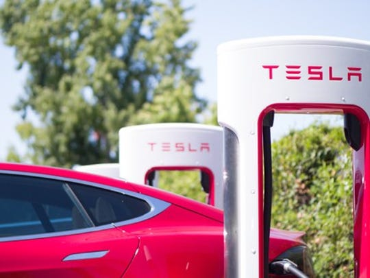 A red Tesla Model S charging at a Supercharger location
