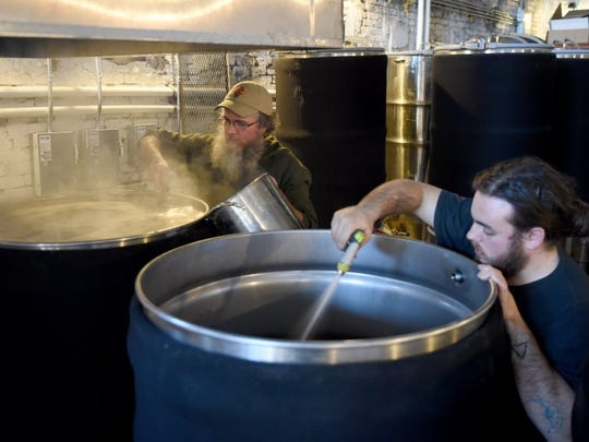 Brewer Jeff Adams, left, and volunteer Nick Blais tend to beer at Crafty Bastard Brewery on Jan. 6, 2016.