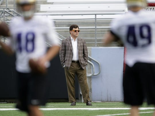 Former Washington and Texas A&M athletic director Scott Woodward, center, watches from the sideline as players take part in practice drills, Monday, March 30, 2015, on the first day of spring NCAA college football practice in Seattle.