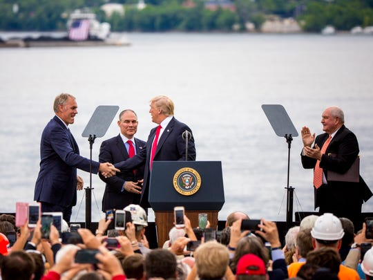 President Donald Trump greets United States Department of the Interior Ryan Zinke and Administrator of the Environmental Protection Agency Scott Pruitt, while United States Secretary of Agriculture Sonny Perdue applauds on stage at Rivertowne Marina in Cincinnati Wednesday, June 7, 2017.