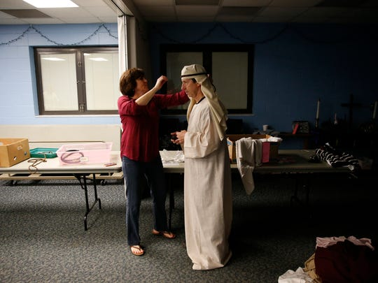 Stacy Etheridge helps Ken Goldsby into his travelers costume during last year's Living Christmas Story at Killearn United Methodist Church.