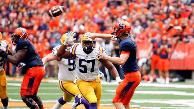 Syracuse quarterback Zack Mahoney (16) throws under pressure from LSU defensive tackle Davon Godchaux (57) during the first half of an NCAA college football game on Saturday, Sept. 26, 2015, in Syracuse, N.Y. (AP Photo/Mike Groll)