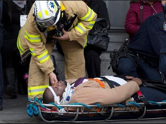 An injured passenger is assisted by an EMS worker as he lies on a gurney outside Atlantic Terminal after a Long Island Rail Road incident, Wednesday, Jan. 4, 2017, in Brooklyn. Officials said a commuter train hit a bumping block as it arrived at the terminal.