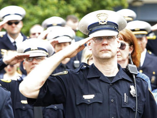 """Police Officer Steve Eder salutes fallen soldiers as """"Taps"""" is played during the 2013 police memorial. The parade and ceremony commemorated Peace Officers Memorial Day and National Police Week."""