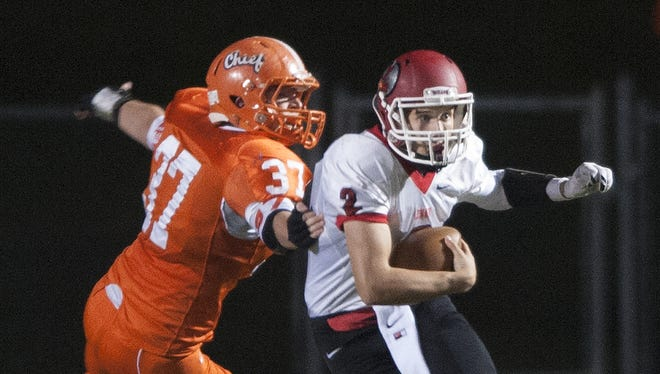 Cherokee's Michael Pawlowski, left, 37, reaches for a tackle against Lenape's Bryce Long, 2, during the first quarter of the game at Cherokee.