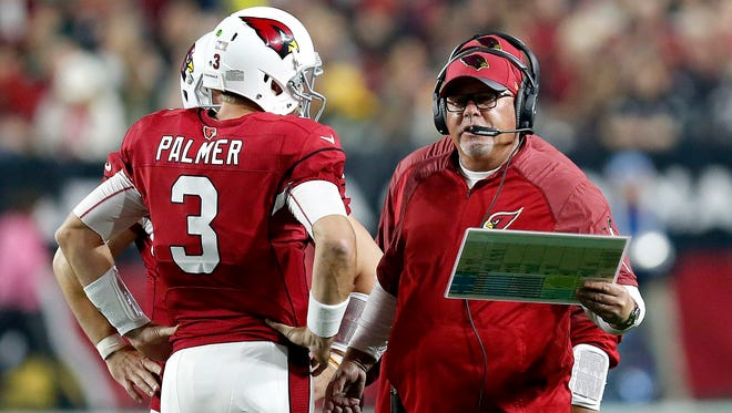 Arizona Cardinals head coach Bruce Arians talks with quarterback Carson Palmer during the first half of an NFL divisional playoff game against the Green Bay Packers on Saturday.