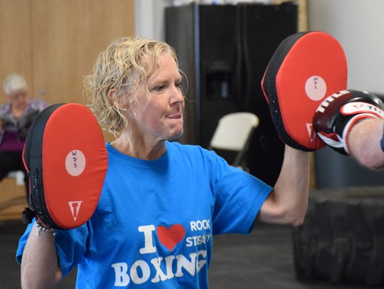 Program director Wendy Shutty holds the boxking mitts