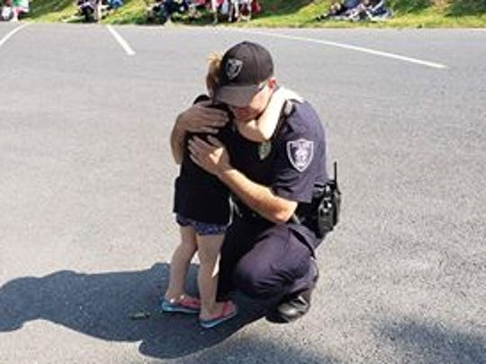 From reader Jessica Burns, her daughter Jordyn Alexander, 5, of Staunton hugs a Staunton police officer before the start of the parade Wednesday, July 4, 2018