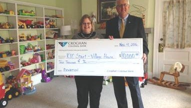 Rick Robertson, President and CEO of Croghan Colonial Bank, and Sue Fuller, executive director of Village House, hold a check illustrating the bank's $10,000 donation to the local charity.