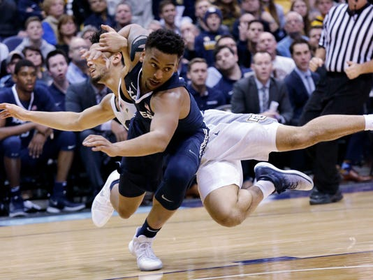 Xavier guard Trevon Bluiett, front, is fouled by Marquette guard Markus Howard during the first half of an NCAA basketball game, Wednesday, Dec. 27, 2017, in Milwaukee. (AP Photo/Darren Hauck)