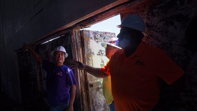 At left, a safety technician with the Navajo Nation Safety and Loss Control Program looks over the interior of the former Boys & Girls Clubs of America building on Thursday in Shiprock.