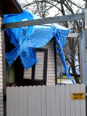 In this 2011 file photo, a tarp covers a side entrance to 122 North St. in Brighton. The house is one of two owned by Marilyn and Leon Bonner and will likely be torn down by Nov. 15 after a recent court ruling.