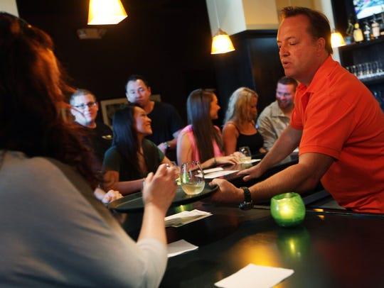 Carl Georigi serves white wine to friends and employees