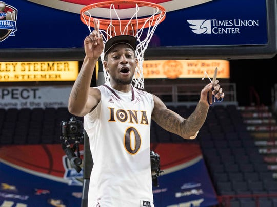 Iona Gaels guard Rickey McGill (0) cuts down the net after the game at Times Union Center.