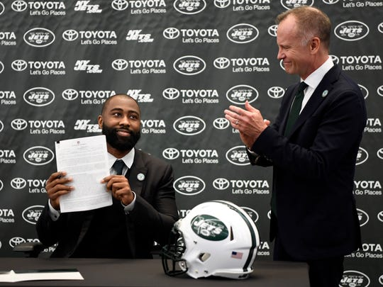 New York Jets owner Christopher Johnson, right, applauds as Darrelle Revis holds up his signed contract before officially retiring as a Jet in Florham Park, NJ on Tuesday, July 24, 2018. Revis signed a contract to formally retire as a Jet.