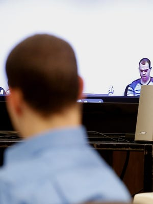 Alexander Kozak watches an interview he gave following his arrest, during his trial Wednesday, April 20, 2016, at the Story County Courthouse in Nevada.