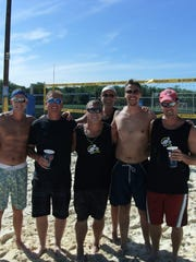 Brian Hawkins (right) was killed Tuesday in a car crash. He is shown here with a group of sand volleyball players at Midwest Sports Complex.