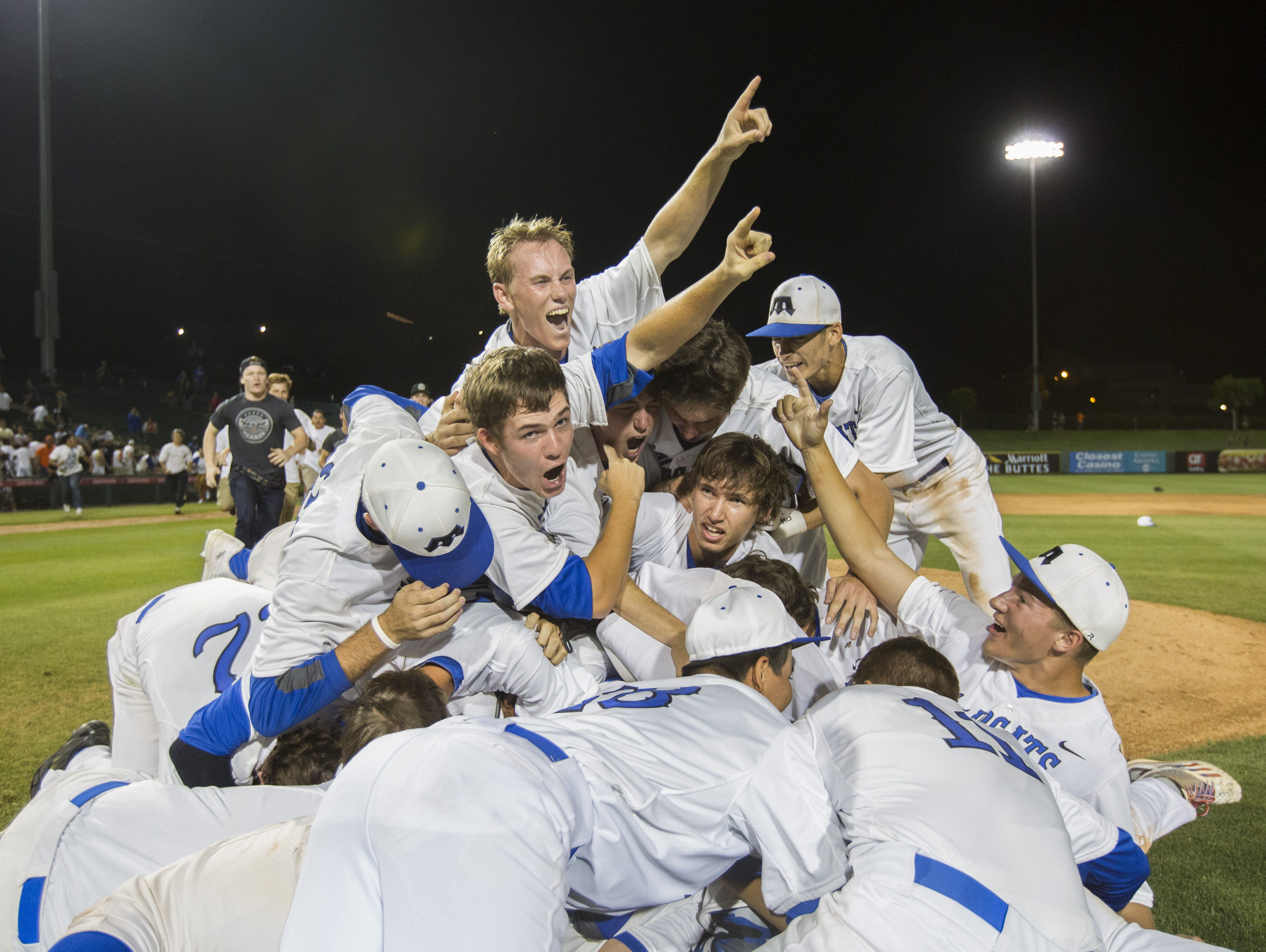 Mesquite players pile ontop of pitcher Josh Webster (12) after the team wins 5-2 over Liberty capturing the D1 State Championship game in at Tempe Diablo Stadium in Tempe, AZ on May 19, 2015.