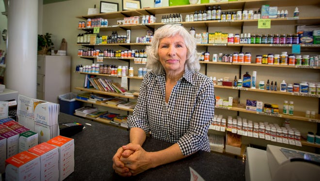 Joan Thomas, who's worked at the Vita-Man Nutrition Center for 25 years, stands behind the counter of the store.