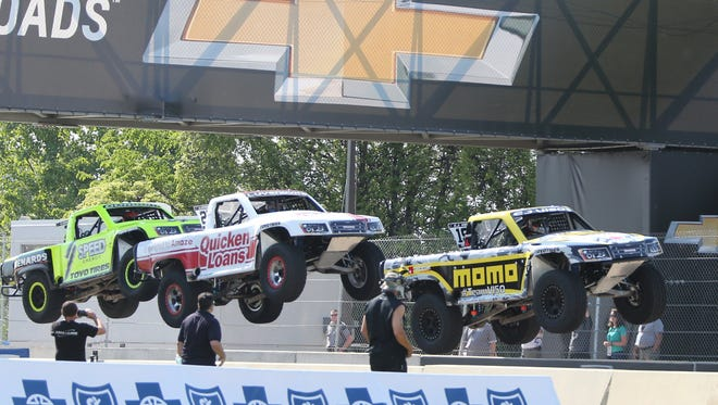 Drivers Robby Gordon, left, Arie Luyendyk Jr., center, and Apdaly Lopez take a jump during the  Stadium Super Truck Series race in Detroit.