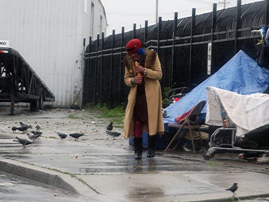A woman clutches her coat during cold and rainy days last winter in Salinas.