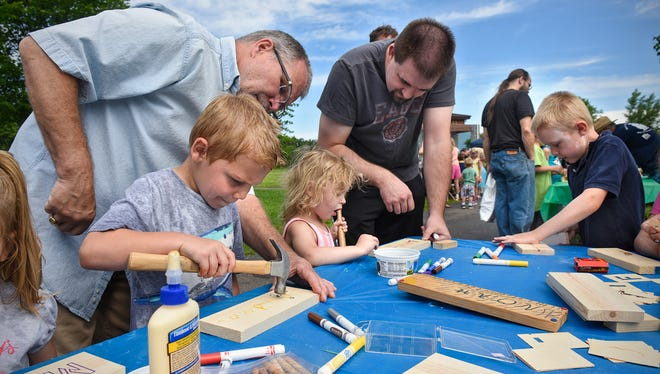 Families work on a craft project Saturday, June 17, during the Celebration of Fatherhood event at Lake George in St. Cloud.