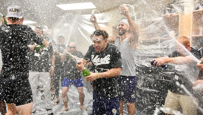 York Revolution's Dayron Varona, center, celebrates with the team in the clubhouse after the Revs won the third game of the five-game Atlantic League Championship series Friday, Sept. 29, 2017, at PeoplesBank Park. The Revolution defeated the Long Island Ducks 3-2 to clinch the championship, their third overall and first since 2011.