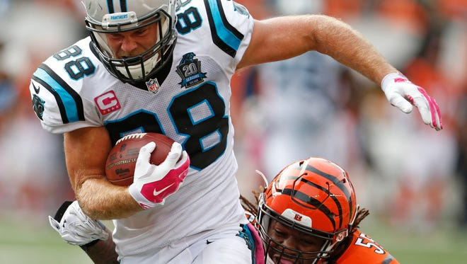 Panthers tight end Greg Olsen is tackled by the Bengals' Vontaze Burfict as he scores a touchdown on Sunday.
