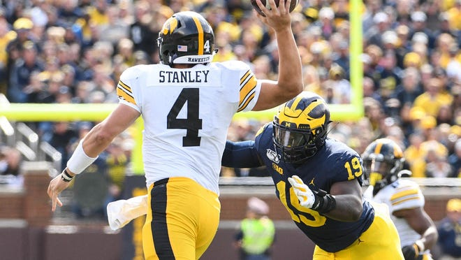 Michigan defensive lineman Kwity Paye, the former Hendricken star, takes aim on Iowa quarterback Nate Stanley during the 2019 season.
