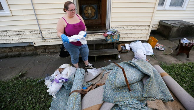 Jennifer Pence looks at the carpet that was removed from her parents' home on Elm Avenue in Norwood on Monday.