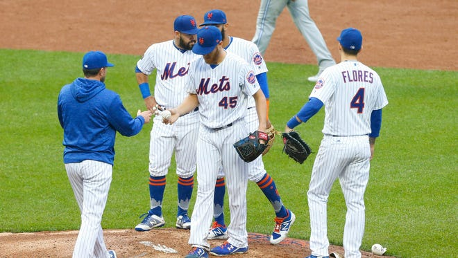 New York Mets manager Mickey Callaway (36) takes the balll from starting pitcher Zack Wheeler (45) in the fifth inning against the Toronto Blue Jays at Citi Field.