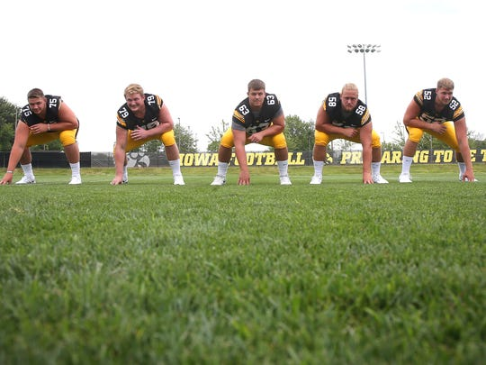 Members of the Iowa offensive line, from left, Ike Boettger, Sean Welsh, Austin Blythe, Eric Simmons, and Boone Myers pose for a photo during the University of Iowa football team's media day on Saturday, Aug. 8, 2015, in Iowa City, Iowa.