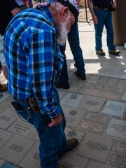 A veteran searches for a familiar name on the memorial pavers at the Vietnam Veterans Memorial.