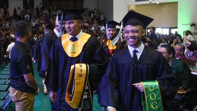 Graduating Tritons make their way through the aisle during the University of Guam Fañomnkån 2018 Commencement Ceremony processional at the UOG Calvo Field House in Mangilao on May 20, 2018.