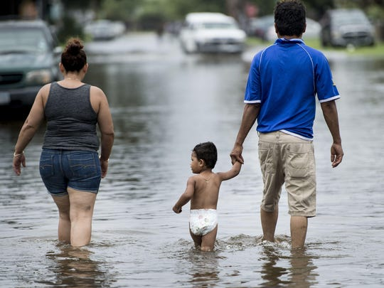 People walk through flooded streets as the effects of Hurricane Harvey are seen August 26, 2017 in Galveston, Texas.
