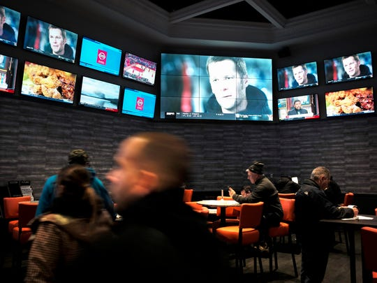 In this Monday, Jan. 28, 2019 photo, patrons visit the sports betting area of Twin River Casino in Lincoln, R.I. New England Patriots fans are gearing up for Super Bowl 53 by betting on the team to win over the Los Angeles Rams, the first time they can do so legally in New England. Rhode Island is the only state in the region that has launched sports betting so far. (AP Photo/Steven Senne)