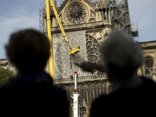 People watch Sunday as workers affix a net to cover one of the iconic stained glass windows of Notre Dame Cathedral in Paris. Some streets around the cathedral reopened, allowing the public to get a closer look after last week's blaze.
